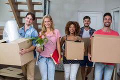 Friends smiling while carrying carton in new house Royalty Free Stock Images