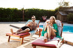 Friends smiling, drinking cocktails, lying on chaises near swimming pool. Royalty Free Stock Images