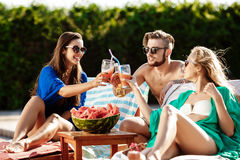 Friends smiling, eating watermelon, drinking cocktails, relaxing near swimming pool. Stock Image