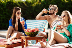 Friends smiling, eating watermelon, drinking cocktails, relaxing near swimming pool. Friends smiling, sunbathing, eating watermelon, drinking cocktails stock photography