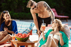 Friends smiling, eating watermelon, drinking cocktails, relaxing near swimming pool. royalty free stock photography