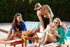 Friends smiling, eating watermelon, drinking cocktails, relaxing near swimming pool. stock images