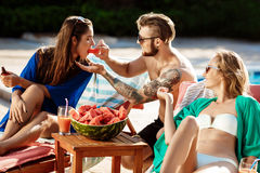 Friends smiling, eating watermelon, drinking cocktails, relaxing near swimming pool. stock photo