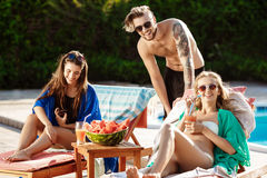 Friends smiling, eating watermelon, drinking cocktails, relaxing near swimming pool. stock photography