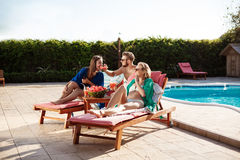 Friends smiling, eating watermelon, relaxing, lying near swimming pool. Stock Image