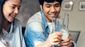 Friends are smiling, happy partying in the bar and talking and clinking bottles with beverages.  royalty free stock image