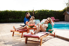 Friends smiling, speaking, sunbathing, lying on chaises near swimming pool. Royalty Free Stock Images