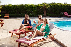 Friends smiling, sunbathing, drinking cocktails, lying near swimming pool. Royalty Free Stock Images