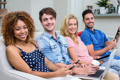 Friends smiling while using technologies on sofa at home Stock Images