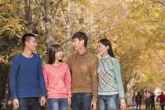 Friends smiling and walking together in park in autumn Stock Photo