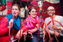 Friends smoking a hookah in shisha lounge Royalty Free Stock Photos