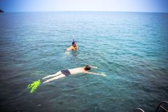 Friends snorkeling in the azure sea near boat Royalty Free Stock Photo