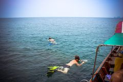 Friends snorkeling in the azure sea near boat Stock Image