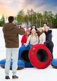 Friends with snow tubes taking photo by tablet pc stock images