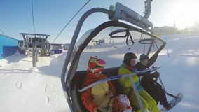 Friends snowboarders riding up ski lift in sunny winter day through the ssun with lens flare effects in slow motion stock video footage