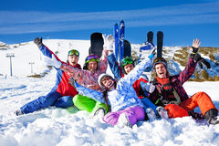 Friends with snowboards lifting hands up Stock Photo