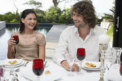 Friends Socialising At Dinner Party Outdoors. Happy young friends sitting near pool socialising at dinner party Royalty Free Stock Image