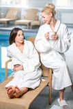 Friends in the spa. Female friends in bathrobes relaxing together near the basin in the spa Royalty Free Stock Photo