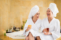 Friends in spa salon. Cheerful women in bathrobes drinking juice: friends in spa salon Stock Photography