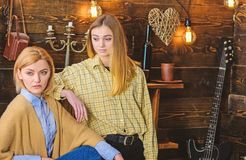 Friends spend pleasant evening in gamekeepers house, interior background. Girls on calm faces enjoy warm atmosphere stock photography