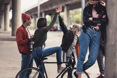 Group of young fashionable people with vintage bike spending time. Together outdoors stock photos