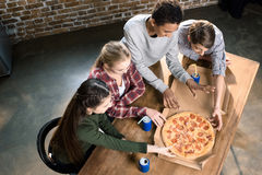 Friends spending time together with pizza and soda drinks, eating pizza at home concept Stock Images