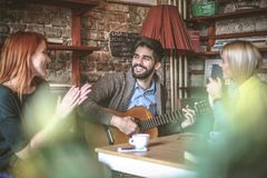 Friends spending time together, singing and play guitar. stock photography