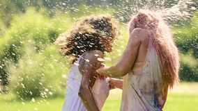 Friends splashing water on girls covered in powder paint at Holi festival. Stock footage stock video footage