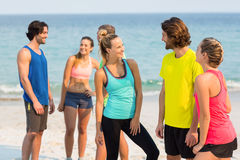 Friends in sports clothing talking while standing at beach Stock Photo