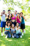 Friends in sportswear showing thumbs up. Group portrait of friends in sportswear showing thumbs up at the park royalty free stock images