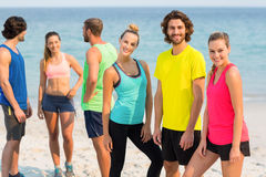 Friends in sportswear standing on shore at beach Stock Image