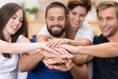 Friends stacking hands. Group of happy smiling young friends stacking hands in a joint effort of cooperation and teamwork with focus to their hands Stock Photography