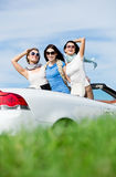 Friends stand in the auto with hands up. Group of girls stands in the auto with hands up. Happy journey of joyful teenagers Royalty Free Stock Image