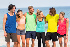 Friends standing with arm around at beach Stock Image