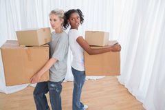 Friends standing back to back holding moving boxes Stock Photo
