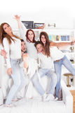 Friends standing on the couch smiling indoors. Happy friends standing on the couch smiling indoors Stock Images