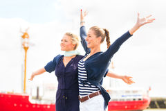 Friends standing at Harbor pier feeling free Stock Photo