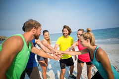 Friends standing with stacked hands at beach Stock Photo