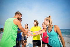 Friends standing with stacked hands on shore Stock Images