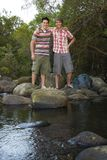 Friends Standing On Stones By River Stock Image