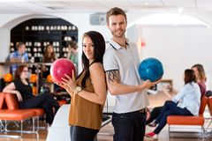 Friends Standing Together With Bowling Balls in Royalty Free Stock Photography