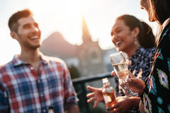 Friends standing together on rooftop with drinks Stock Photos