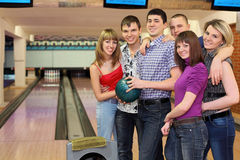 Friends stay in bowling club. One fellow holds ball for bowling and his friends stand alongside with him and smile, focus on  fellow in center and on girls on Stock Photography