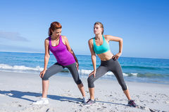 Friends stretching together beside the water Stock Images