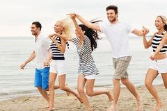 Friends in striped clothes running along beach royalty free stock images