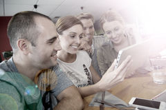 Friends students enjoying in snack bar using a tablet Royalty Free Stock Photography