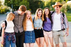 Friends students hugging walking in the city. Friendship, youth, happiness, campus life, relationships, togetherness. Group of young friends students hugging royalty free stock photography