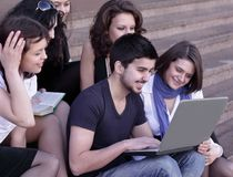 Friends of the students looking at the laptop screen. Education concept Stock Photo