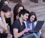 Friends of the students looking at the laptop screen. Education concept Stock Photos