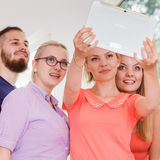 Friends students taking self photo with tablet. Fun bonding selfie concept. Group of diverse friends students classmates taking self photo with tablet pc royalty free stock image